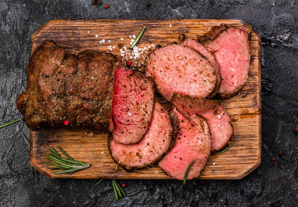 Roast beef sliced with herbs and salt around the edges on a chopping board